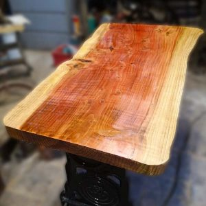 wany edge timber table mounted on old mangle base